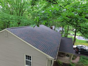 A new asphalt shingle roof on a residential home with beige siding.