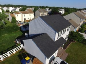 Aerial image of a white two-story home in a suburban neighborhood with a gray asphalt shingle roof.